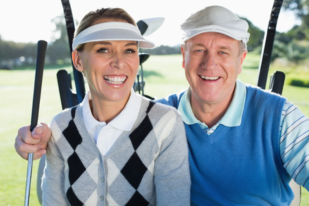 Happy golfing couple sitting in golf buggy smiling at camera on a sunny day at the golf course photo