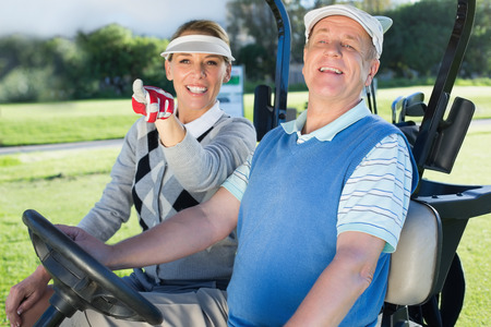 Happy golfing couple sitting in golf buggy looking around on a sunny day at the golf course photo