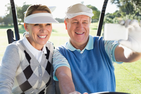 Happy golfing couple sitting in golf buggy taking a selfie on a sunny day at the golf course photo
