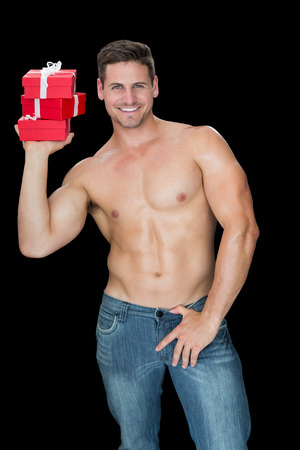 Muscular man holding pile of presents in blue jeans on black background photo