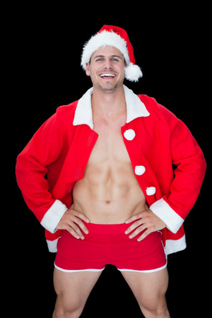 Smiling muscular man posing in sexy santa outfit on black background photo