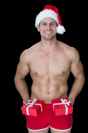 Smiling muscular man posing in sexy santa outfit offering gifts on black background Stock Photo