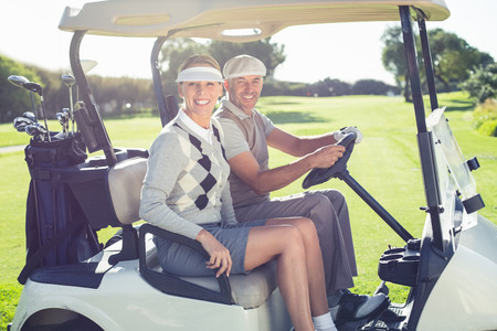 Happy golfing couple sitting in buggy smiling at camera on a sunny day at the golf course