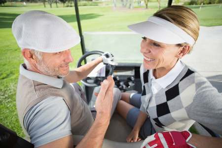 Golfing couple smiling at each other in their golf buggy on a sunny day at the golf course photo