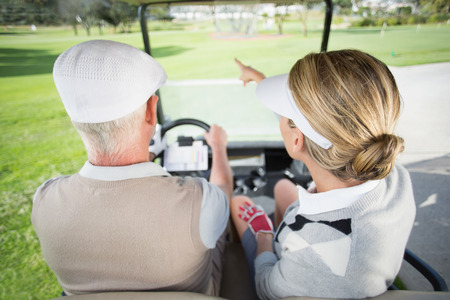 Golfing couple driving in their golf buggy with woman pointing on a sunny day at the golf course photo