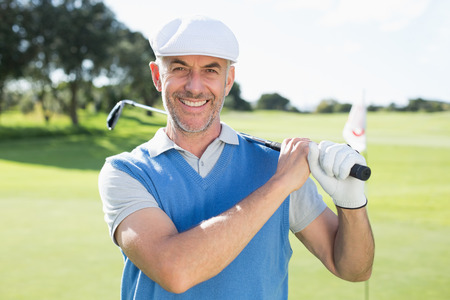 Golfer standing and swinging his club smiling at camera on a sunny day at the golf course photo