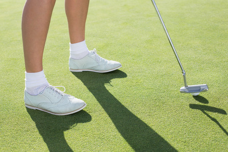 Lady golfer on the putting green on a sunny day at the golf course Stock Photo