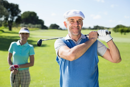 Happy golfer teeing off with partner behind him on a sunny day at the golf course photo
