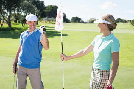 eighteenth: Lady golfer holding eighteenth hole flag for cheering partner on a sunny day at the golf course