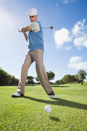 Golfer swinging his club on the course on a sunny day at the golf course photo
