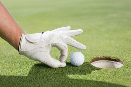 flicking: Golfer trying to flick ball into hole on a sunny day at the golf course