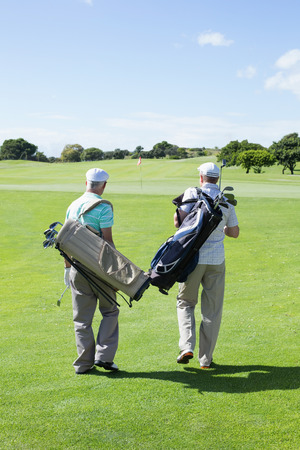 Golfer friends walking and holding their golf bags on a sunny day at the golf course photo