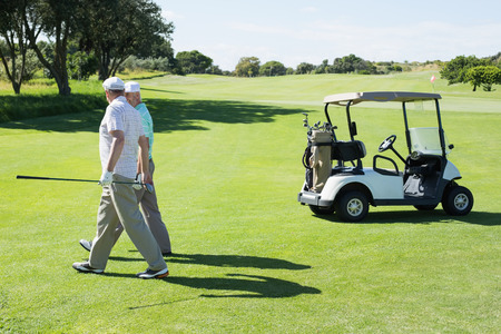 Golfing friends walking beside their buggy on a sunny day at the golf course photo
