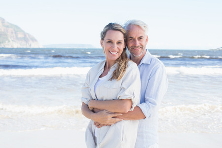 escapism: Happy couple hugging on the beach woman looking at camera on a sunny day Stock Photo