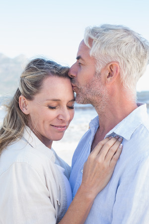 Man kissing his smiling partner on the forehead at the beach on a sunny day photo
