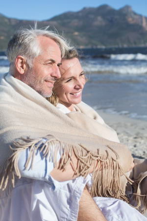 hair wrapped up: Smiling couple sitting on the beach under blanket on a sunny day Stock Photo