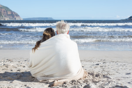 hair wrapped up: Couple sitting on the beach under blanket looking out to sea on a sunny day
