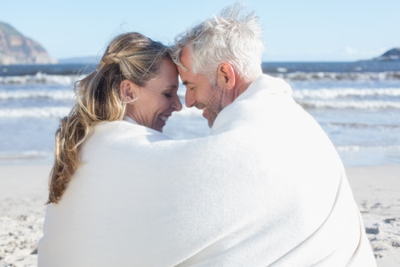 hair wrapped up: Couple sitting on the beach under blanket smiling at each other on a sunny day