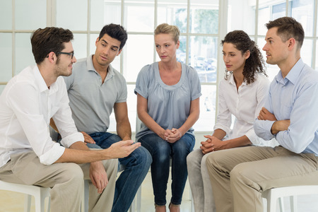 Group therapy in session sitting in a circle in a bright room Stock Photo