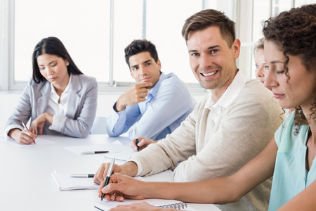 Casual businessman smiling at camera during meeting in the office photo