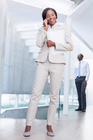 Estate agent talking on phone with buyer in background in a new house photo