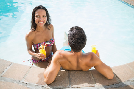 Attractive couple drinking cocktails in the pool on a sunny day photo