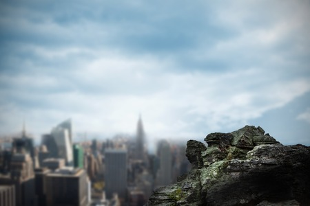 overlooking: Digitally generated large rock overlooking big city