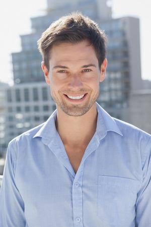 uomo felice: Handsome man smiling at camera on his balcony on a sunny day Archivio Fotografico