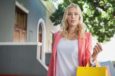 Pretty blonde holding shopping bags on a sunny day in the city Stock Photo