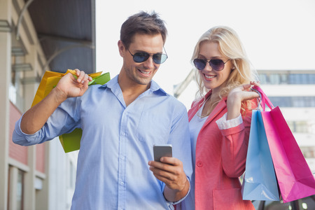 Stylish young couple looking at smartphone holding shopping bags on a sunny day in the city photo