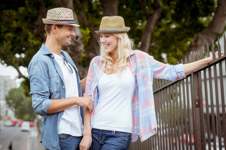 Hip young couple standing by railings on a sunny day in the city photo