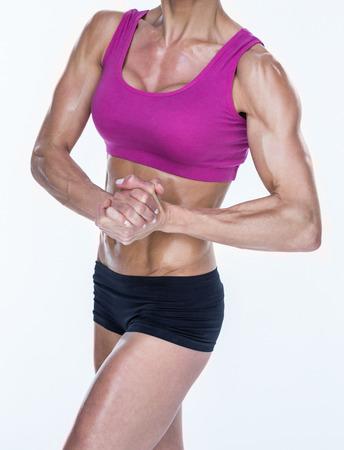 mani unite: Bodybuilder femminile che propone con le mani insieme su sfondo bianco