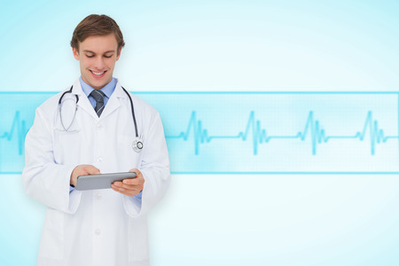 Young doctor using tablet pc against medical background with blue ecg line photo