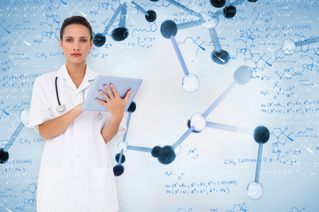 Pretty nurse using tablet pc against notes of biotechnology and genes Stock Photo