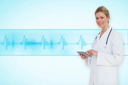 Blonde doctor using tablet pc against medical background with blue ecg line photo