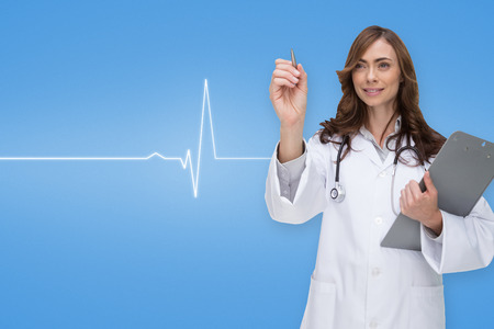 Smiling doctor pointing against medical background with blue ecg line photo