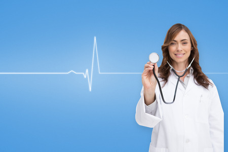 Happy doctor using stethoscope against medical background with blue ecg line photo