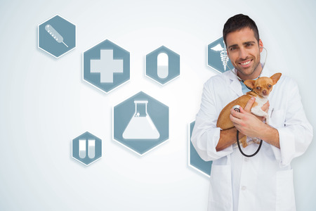 Happy vet checking dog with stethoscope against blue medical interface with icons photo