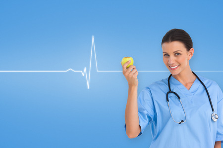 Happy surgeon holding an apple and smiling at camera against medical background with blue ecg line photo