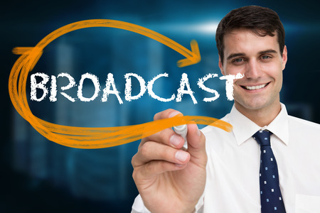 Businessman writing the word broadcast against shiny cityscape on black background photo