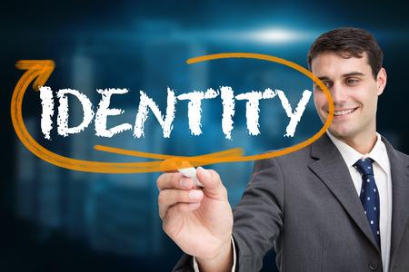 Businessman writing the word identity against shiny cityscape on black background photo