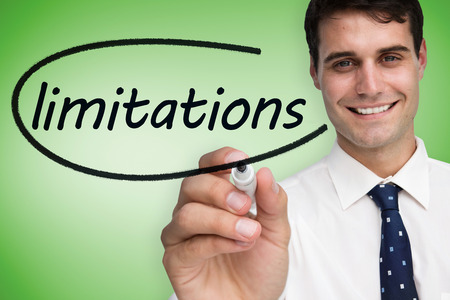 limitations: Businessman writing the word limitations against green vignette