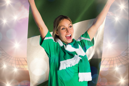 Cheering football fan in green jersey holding nigeria flag against large football stadium under bright blue sky photo