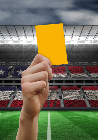 Hand holding up yellow card against stadium full of usa football fans photo