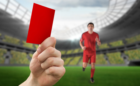 Hand holding up red card against football stadium and player photo