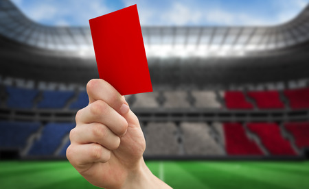 Hand holding up red card against stadium full of france football fans photo