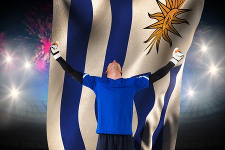 Goalkeeper celebrating a win against fireworks exploding over football stadium and uruguay flag photo