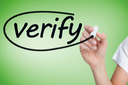 confirm confirmation: Businesswoman writing the word verify against green vignette Stock Photo
