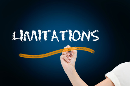 limitations: Businesswoman writing the word limitations against blue background with vignette