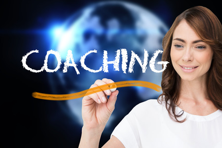 Businesswoman writing the word coaching against glowing earth with binary code photo